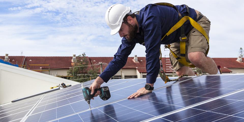 Monteur plaatst zonnepanelen op een dak