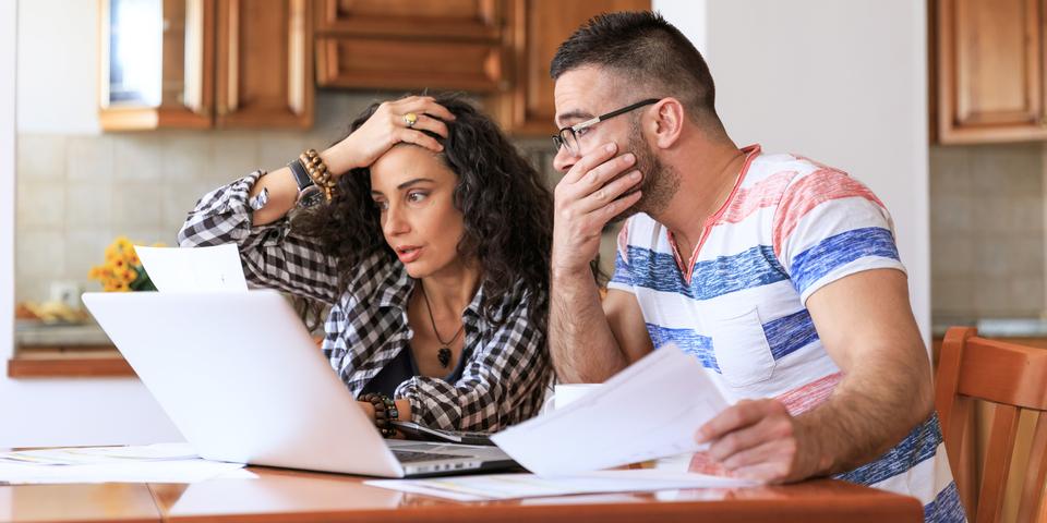 Een vrouw en man in de weer met computer en papieren