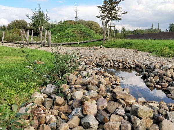 Speelterrein met keien, water en een boomstammenparcours