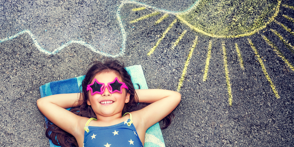 Kind dat aan het zonnen is met een krijttekening achter haar