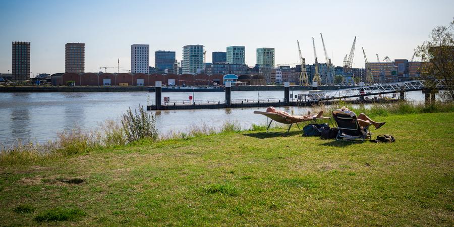 Twee mensen liggen te zonnen aan het Sint-Annastrand op Antwerpen-Linkeroever.