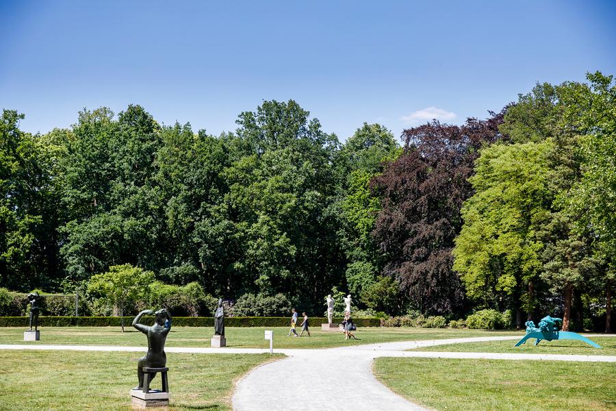 Een zicht op enkele beelden in het park met het bos op de achtergrond.