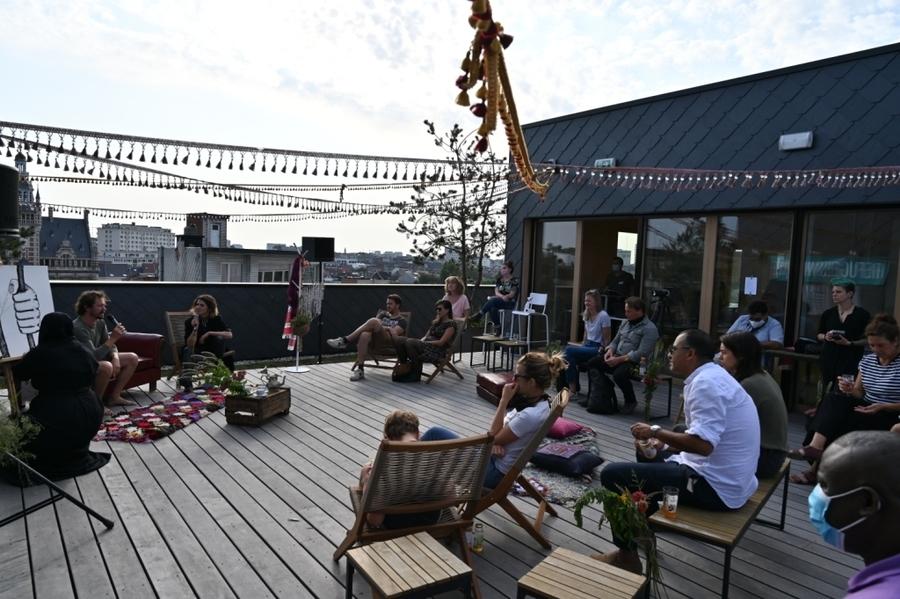 Mensen luisteren naar een verteller, zicht op de daken van Borgerhout