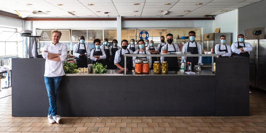 Chef-kok Seppe Nobels poseert met zijn team in een restaurant.