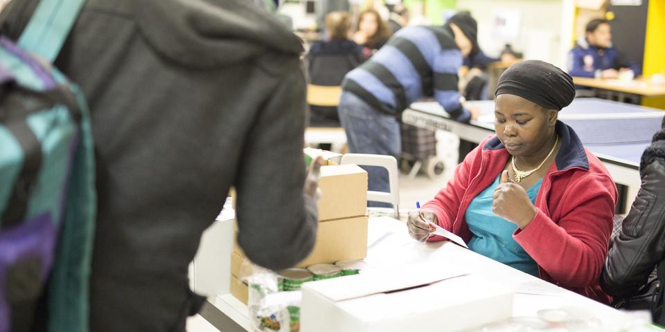 Een vrijwilliger helpt bij de voedselopslag.