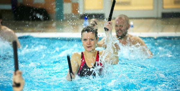 Vrouw doet mee aan een aquagymles in het zwembad