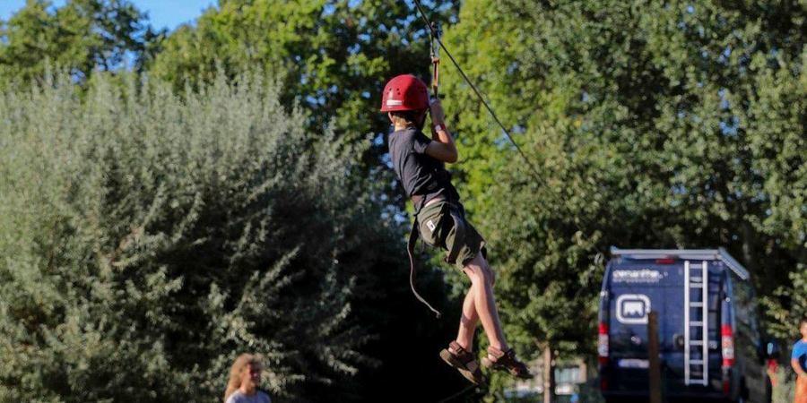 Een kind met helm hangt aan een zipline.
