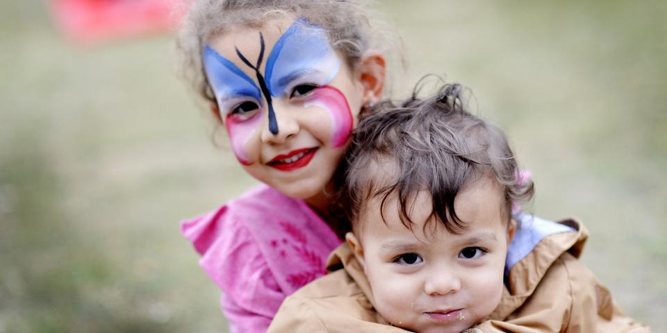Een jong meisje geschminkt als een vlinder en een jonge jongen.