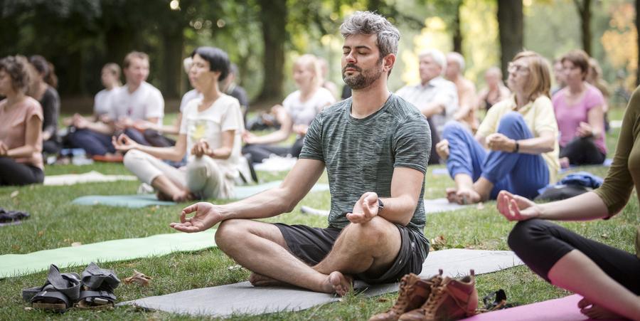 Een groep mensen doet aan yoga in het park