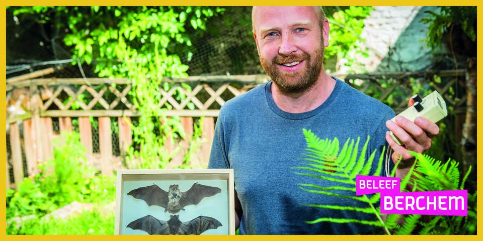 Kris Boers poseert met enkele opgezette vleermuizen en een batdetector.