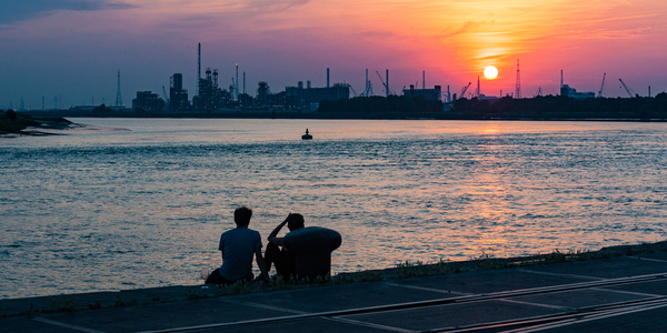 Twee mensen zitten op de Scheldekaaien en kijken bij zonsondergang naar de haven.
