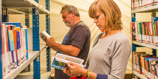 Bezoekers kiezen boeken tijdens de boekenverkoop in bibmagazijn Kotter