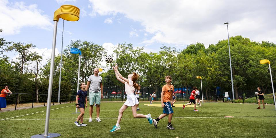 Meisje gooit de bal naar de korf tijdens een korfbal- en omnisportkamp op een zomers openluchtveld