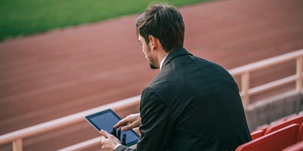 Man met tablet langs de kant van een sportveld