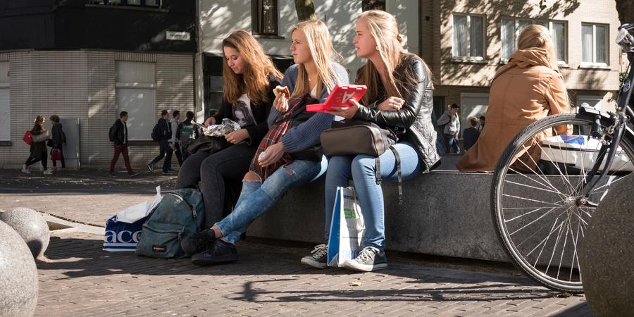 Drie vrouwelijke studenten zitten naast elkaar op een bankje in de universiteitsbuurt.