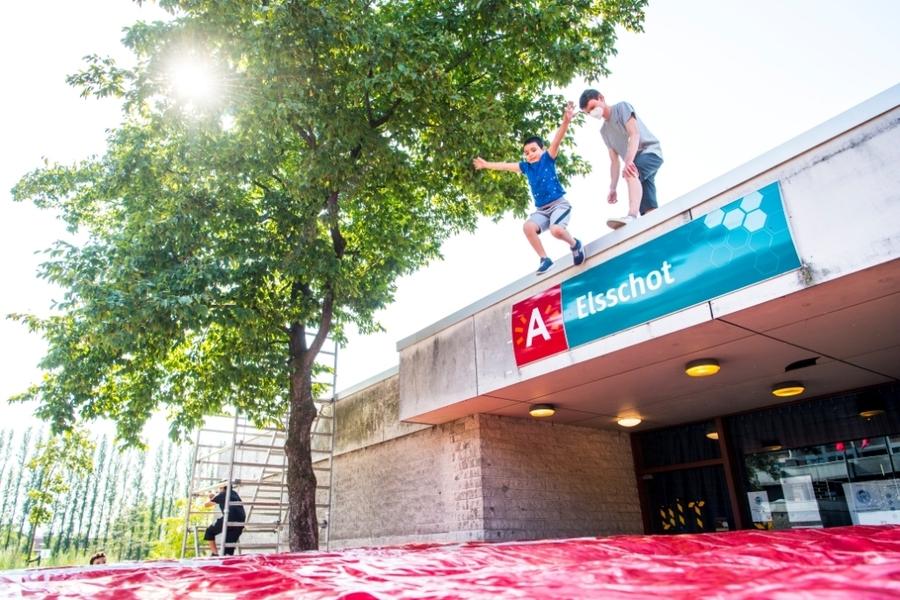 Een jongen springt van het dak naar een valmat