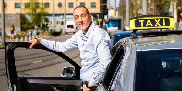Taxichauffeur poseert naast zijn taxi