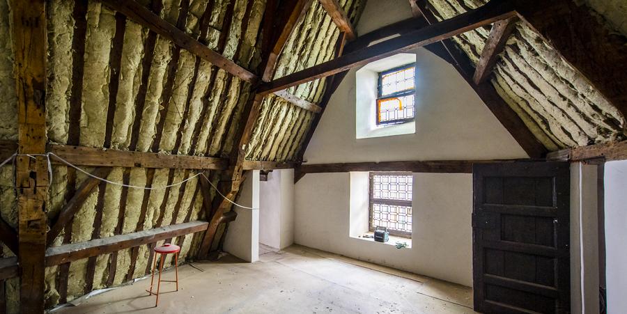 Zolderkamer van het steen, de isolatie en oude houten balken zijn te zien