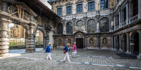 Drie bezoekers wandelen door de portiek van Rubenshuis