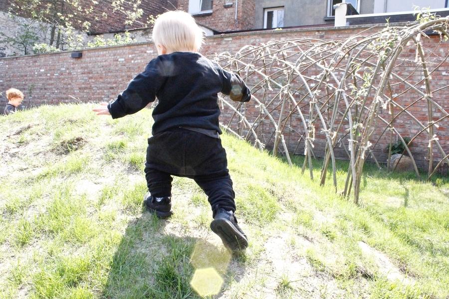 Kind klimt op groene heuvel