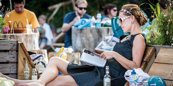 Dame in zomerjurk leest een boek in de zomerbar