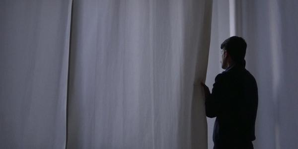 Man staart door raam