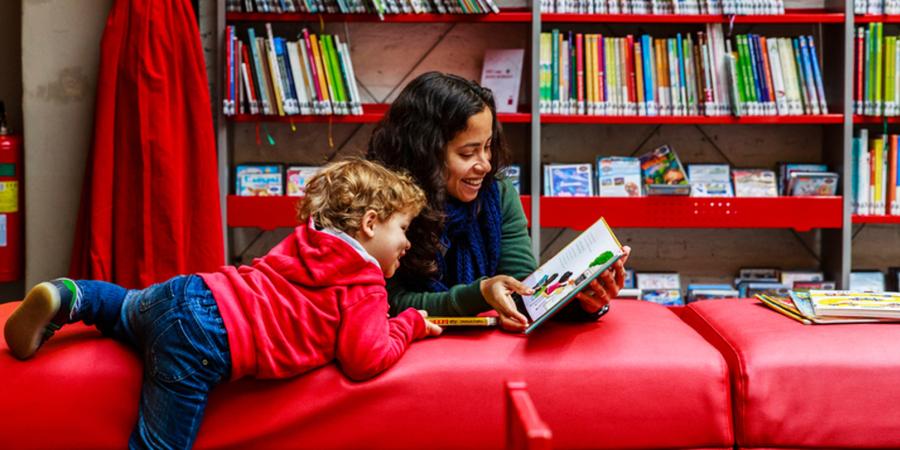 Een vrouw helpt een kindje bij het lezen