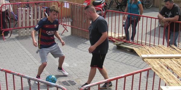 Twee jongeren spelen voetbal op een panna-veldje