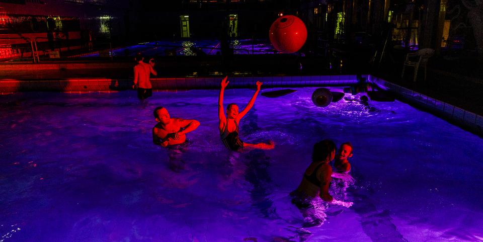 Familie speelt met de 'oogbal' tijdens het Halloweenzwemmen in een sfeervol uitgelicht Antwerps zwembad