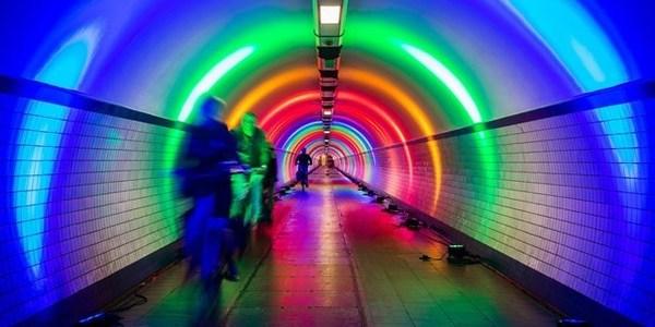 Fietsers in voetgangerstunnel verlicht met regenboogkleuren.