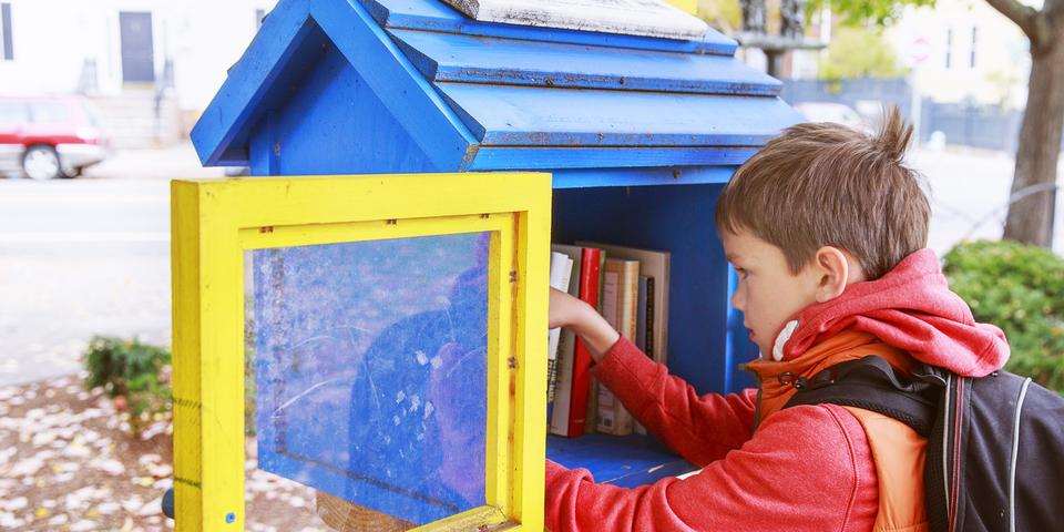 Jongetje kijkt in een ruilboekenkastje