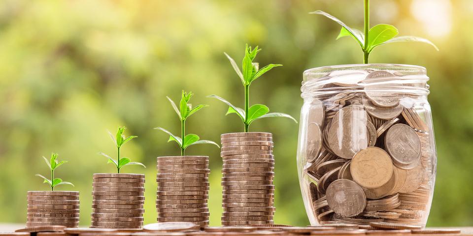 wie zien stapels munten en een bokaal vol munten, hiermee willen we het principe Pay for Performance uitbeelden