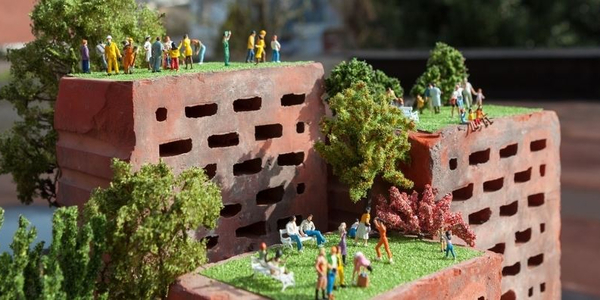 Miniatuurmensen staan op bakstenen
