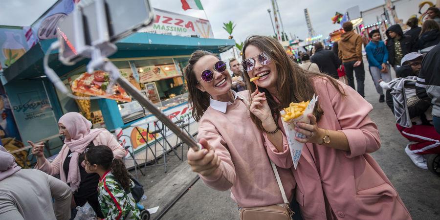 Twee jongedames met flitsende zonnebrillen maken een selfie, pak friet in de hand