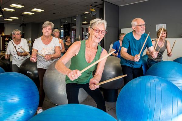Vijftigers trommelen met stokjes op een yogabal