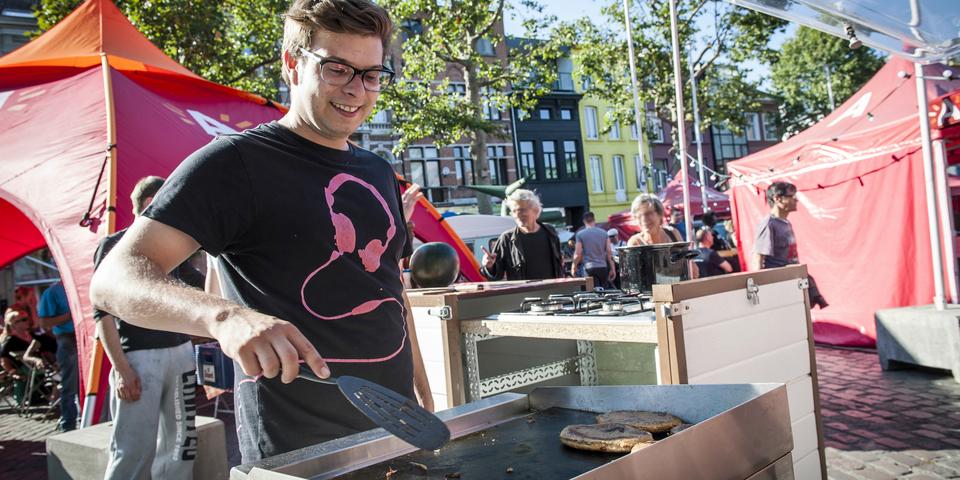 Een man kookt tijdens een buurtfeest.