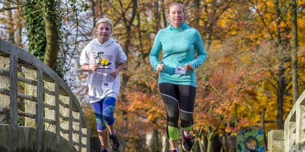 Moeder en dochter aan het lopen over een brug in het park