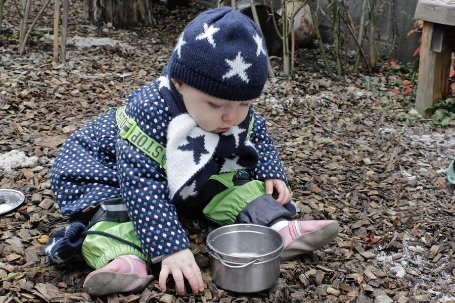 Peuter in warme kleren en regenpak speelt op de grond