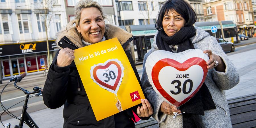 Twee dames poseren met een affiche en een ballon waarop 'zone 30' staat.