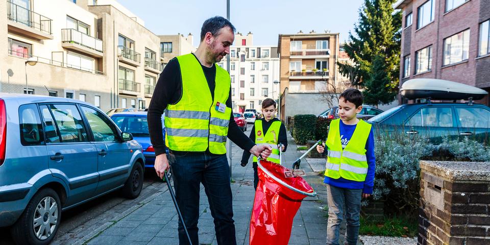 vader en zonen ruimen straatvuil op