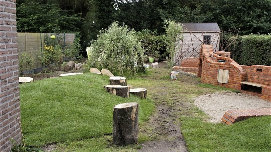 Een heuvel, boomstammen, zandbak, wilgencreaties en tengelmuur