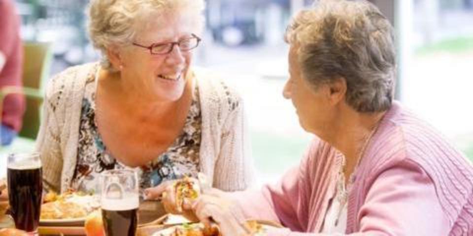 Twee vrouwen die aan het lunchen zijn in een dienstencentrum