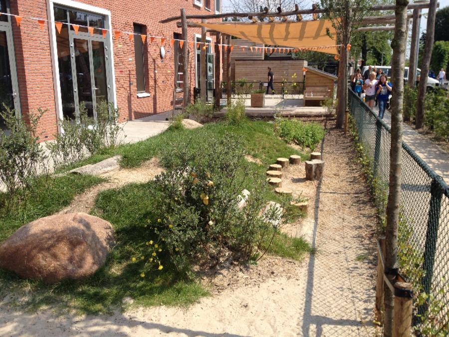 Tuin met verschillende paadjes, boomstronken, een zitsteen, gras en een podium
