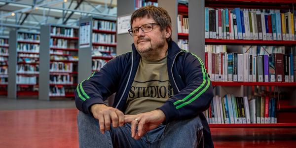 Nigel Williams zit in de bibliotheek