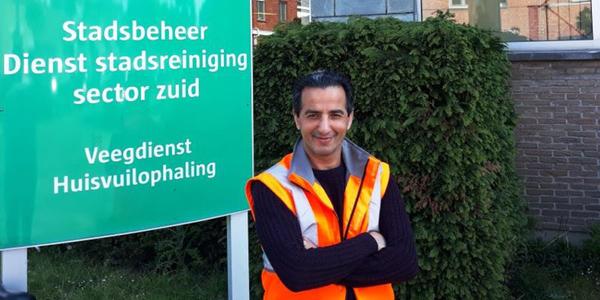 Karim, ploegleider bij de stad, staat voor een bord van de huisvuilophaling