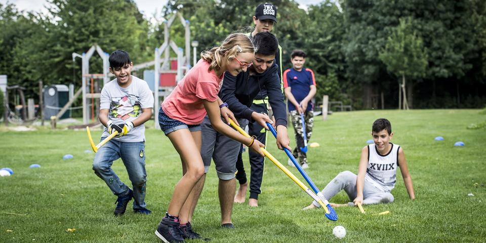 Kinderen spelen hockey in het gras