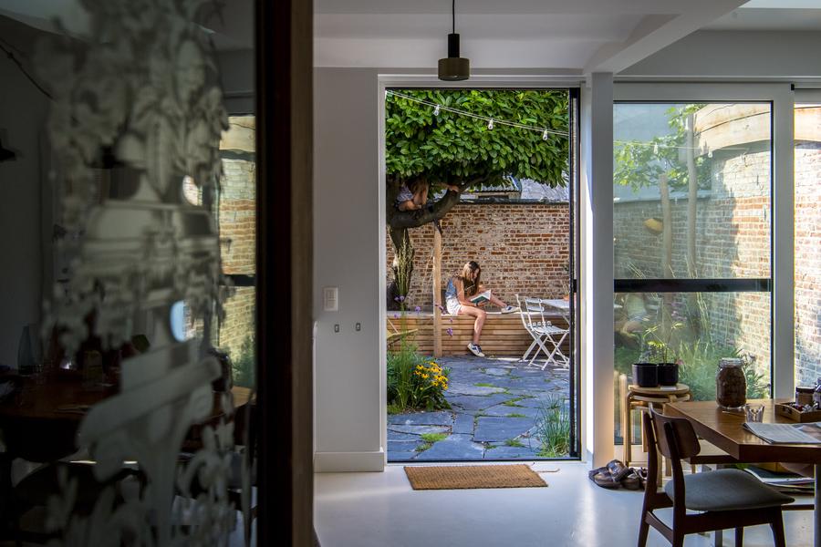 Vanuit de leefruimte kijken we uit op de tuin, waar een meisje zit te lezen op een houten platform.
