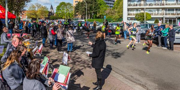 De Harmonie Sint-Bavo en inwoners van het Valaar moedigen de marathonlopers aan.