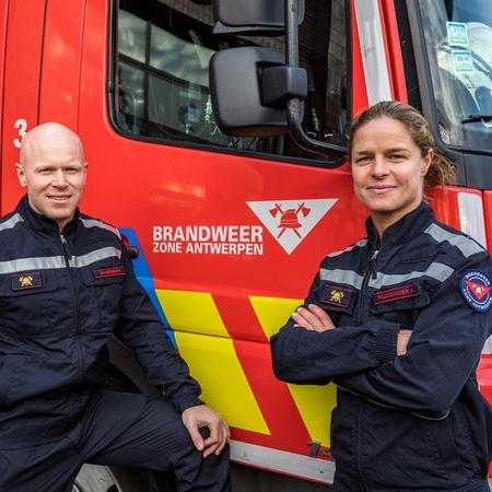 De twee brandweerlieden voor een autopomp van Brandweer Zone Antwerpen