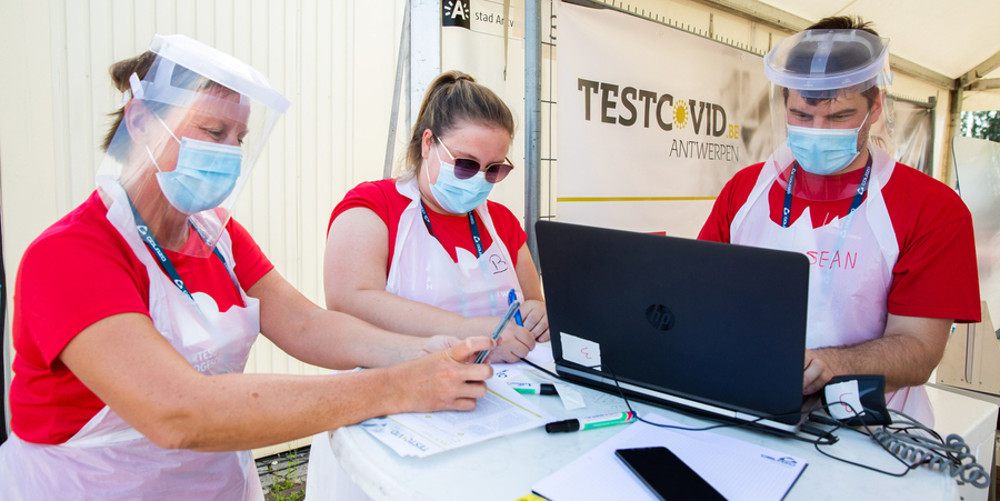 Drie medewerkers van het testdorp TestCovid staan aan een tafel waarop een laptop staat en enkele papieren liggen.
